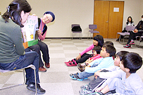 Children listening attentively to volunteers reading aloud a picture book