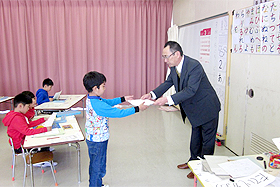 "Child receiving a certificate of completion at the ""graduation"" ceremony. It seems that the children have all become somewhat stronger."