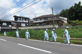 Divided into two groups, the cleanup participants walk about 1 km from the company along National Route 422.